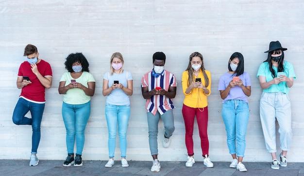 Jongeren die veiligheidsmaskers dragen met slimme mobiele telefoons terwijl ze tijdens de coronavirustijd sociale afstand houden