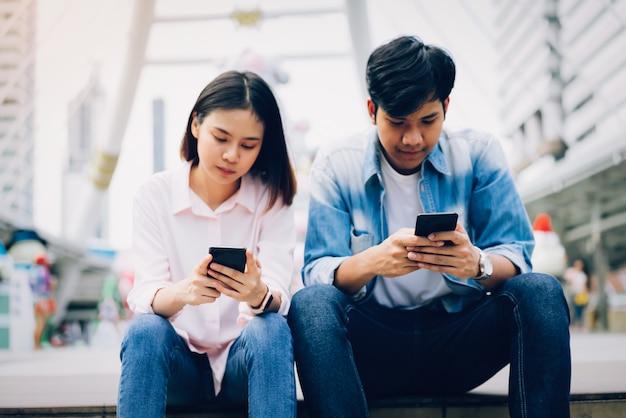 Jongeren gebruiken een smartphone en glimlachen terwijl ze op vrije tijd zitten. technologie concept