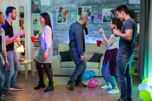 Jongeren genieten van hun tijd samen op een feestje dansen en alcohol drinken.