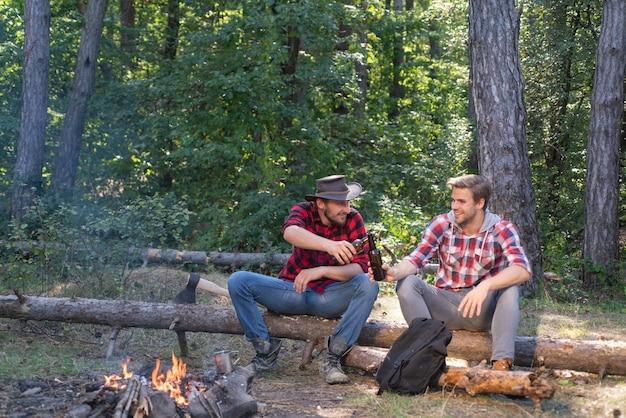 Jongeren genieten van picknick in het park op zomerdag en drinken biergroep van twee mannelijke vrienden campi...