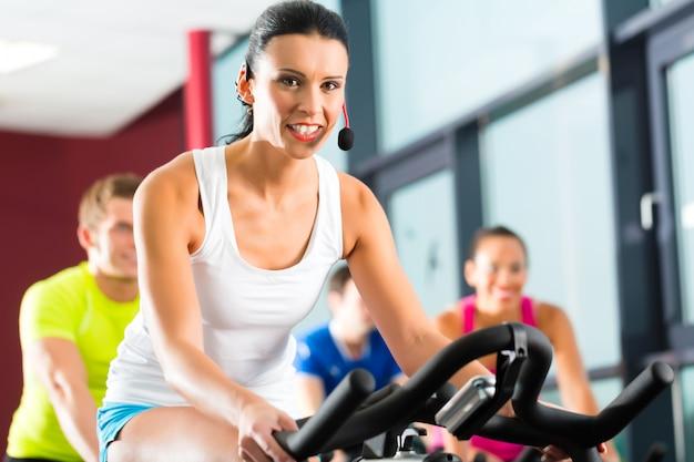 Jongeren, groep vrouwen en mannen die sport doen spinning in de sportschool voor fitness