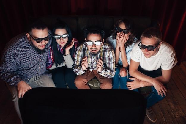 Jongeren in 3d-bril kijken tv op de bank