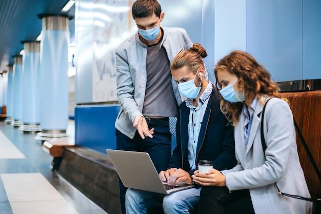 Jongeren in beschermende maskers met behulp van een laptop op het metroplatform