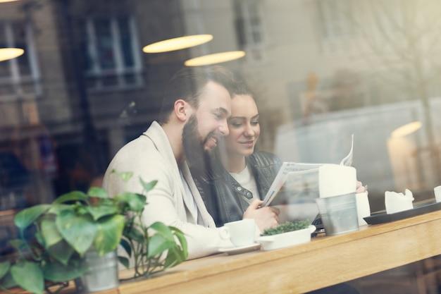 Jongeren in café kijken naar gids