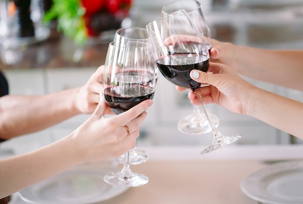 Jongeren in een restaurant dat wijn drinkt op de achtergrond die een kok voorbereidt.