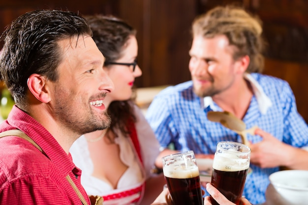 Jongeren in traditionele beierse tracht eten met worstjes in restaurant of pub lunch of diner
