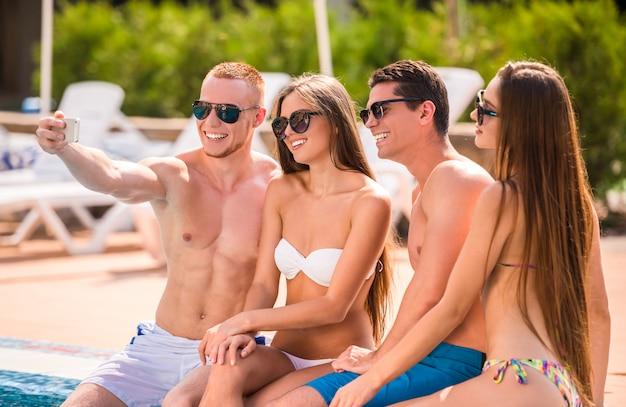 Jongeren in zwembad, glimlachend en selfie maken.