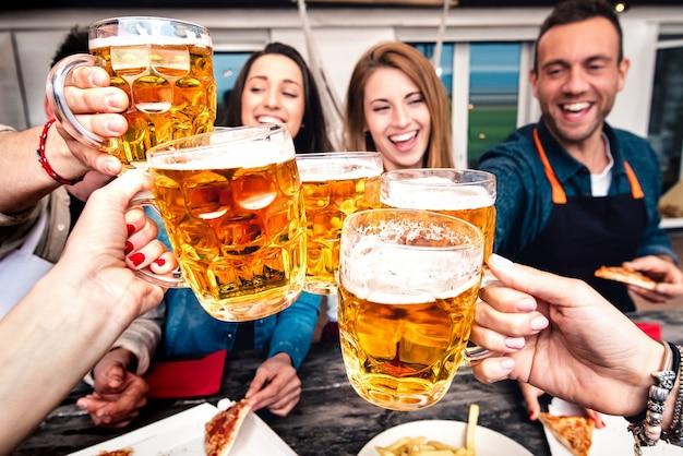 Jongeren standpunt tijdens het roosteren van bier thuis terras na het werk - vriendschap levensstijl concept met gelukkige vrienden die samen genieten van tijd en plezier hebben met het drinken van brouwen pinten - focus op een bril