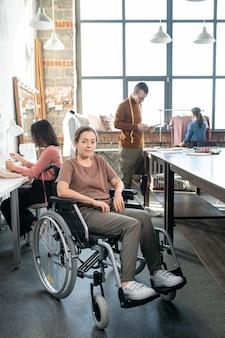 Jongeren uitschakelen naaister in vrijetijdskleding zittend in rolstoel voor camera tegen collega's die werken aan nieuwe modecollectie