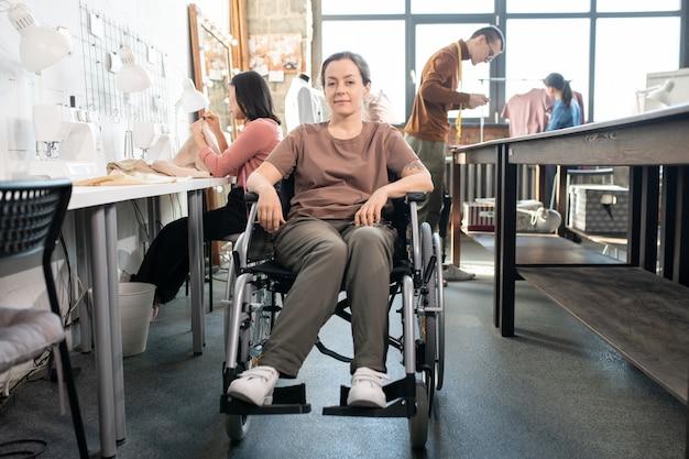 Jongeren uitschakelen vrouw in vrijetijdskleding zittend in rolstoel door werkplek tegen groep collega's die werken aan nieuwe modecollectie