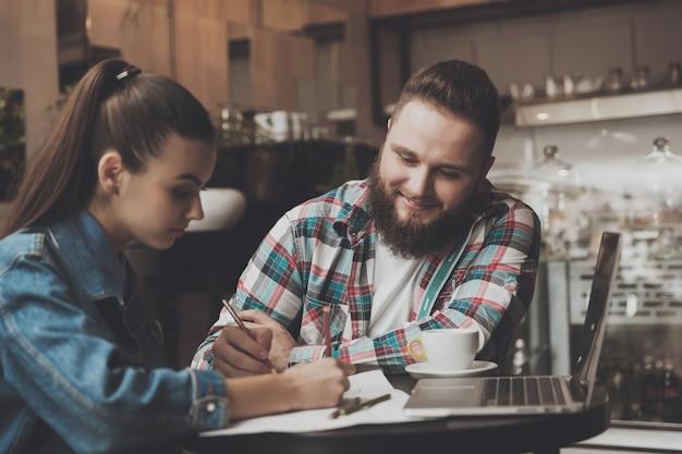 Jongeren vullen documenten in een café in