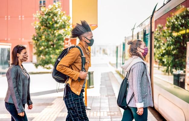Jongeren wachten in overeenstemming met sociale afstand op het busstation in de stad