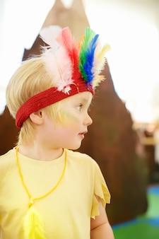 Jongetje betrokken bij kindertheatervoorstelling studio in de rol van de indiaan.