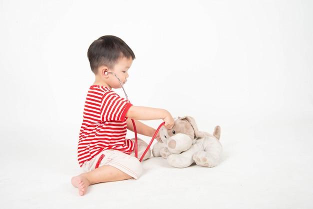 Jongetje doet zich voor als een arts die hond pop controleert