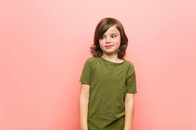 Jongetje haalt schouders op en open ogen verward.
