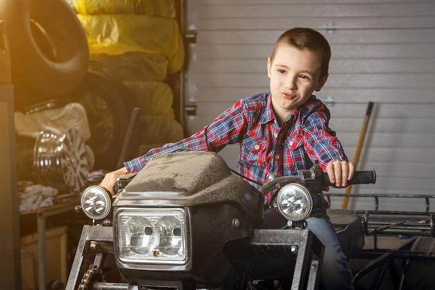Jongetje jonge automonteur droomt vrolijk dat hij snel op een motorfiets rijdt in de garage van een tankstation.