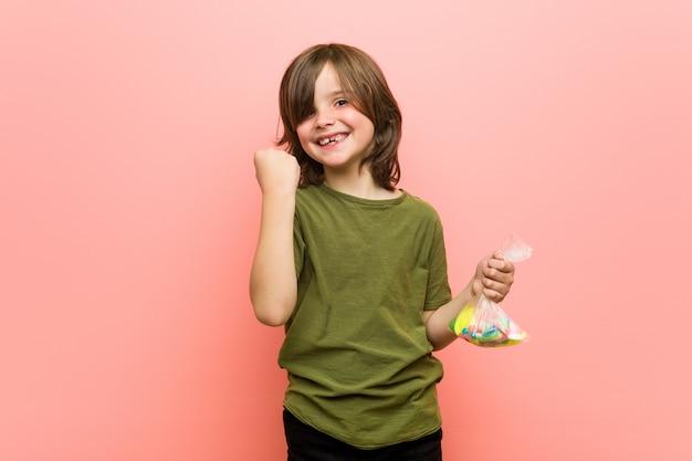 Jongetje kaukasisch bedrijf snoepjes zorgeloos en opgewonden juichen. overwinning concept.