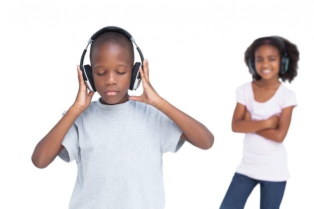Jongetje met gesloten ogen luisteren naar muziek met zijn zus