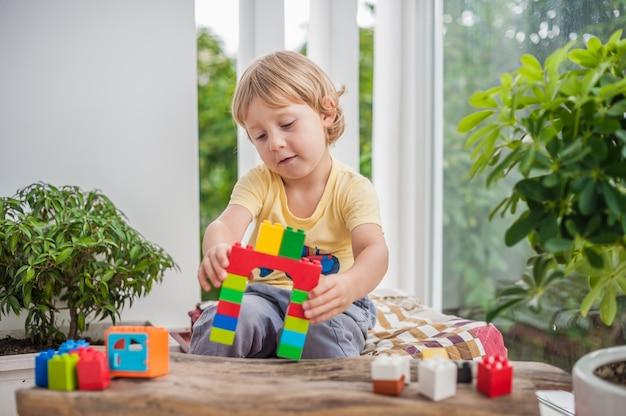 Jongetje met spelen met kleurrijke plastic blokken binnen