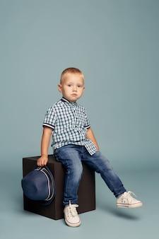 Jongetje poseren, vrolijke emoties jongen model. een mooi kind speelt springen en grimassen zittend op een kubus op een heldere. ,