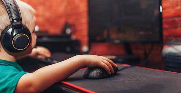 Jongetje spelen van games op computer in hoofdtelefoons met microfoon, computerspel