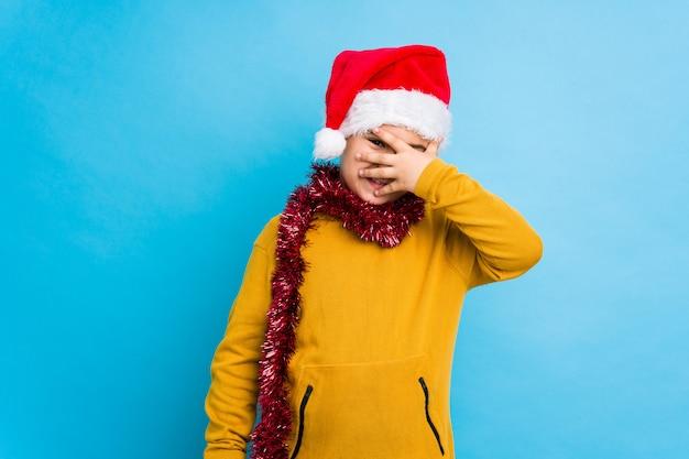 Jongetje vieren kerstdag dragen een kerstmuts geïsoleerd knipperen naar de camera door vingers, beschaamd bedekkend gezicht.