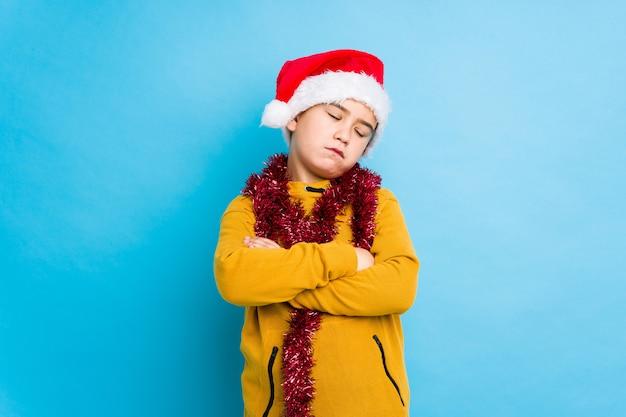 Jongetje vieren kerstdag dragen een kerstmuts geïsoleerd moe van een repetitieve taak.