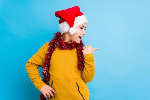 Jongetje vieren kerstdag dragen een kerstmuts geïsoleerde punten met duim vinger weg, lachen en zorgeloos.