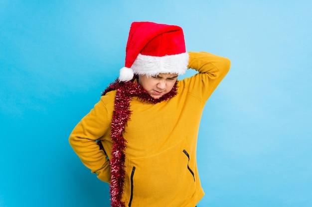 Jongetje vieren kerstdag dragen van een kerstmuts geïsoleerd lijden nekpijn als gevolg van sedentaire levensstijl.