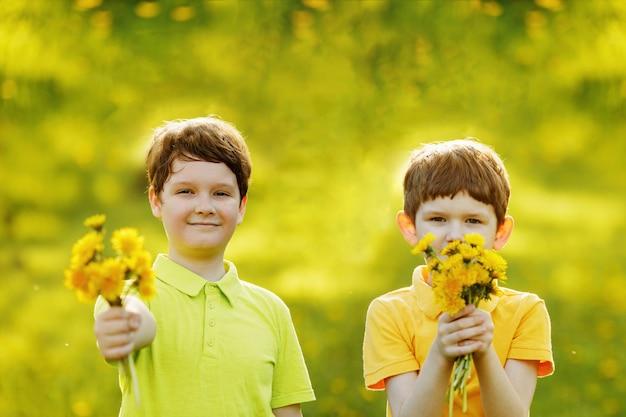 Jongetjes geven een boeket gele paardebloemen aan zijn moeder of vriendin. mama, 8 maart dagconcept.