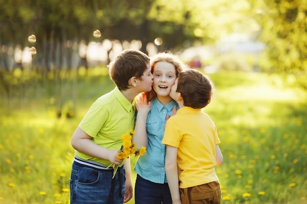 Jongetjes geven zijn vriendin een bouqet van gele paardebloemen.