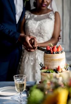 Jonggehuwde paar handen snijden taart samen
