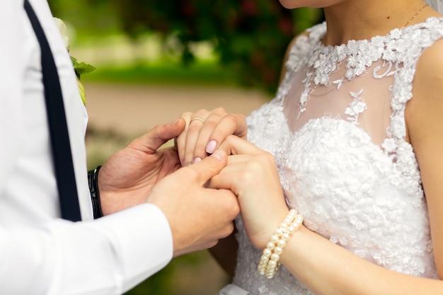 Jonggehuwde paar in trouwjurken hand in hand