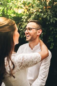Jonggehuwde paar kijken naar elkaar en glimlachen op hun trouwdag. hou van concept.