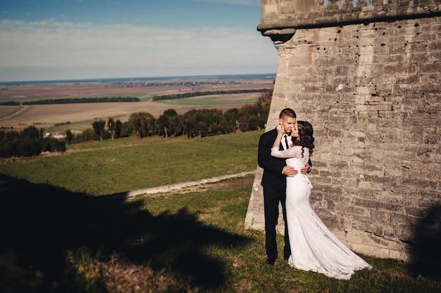 Jonggehuwde paar poseren in de buurt van oud kasteel
