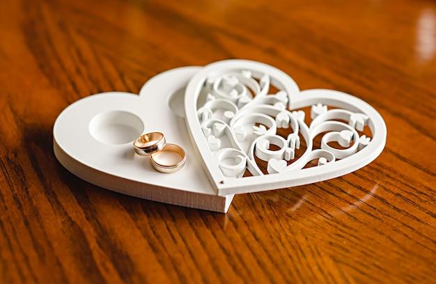 Jonggehuwde trouwringen op een houten hartvormige standaard