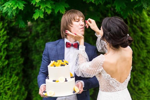 Jonggehuwden en bruidsmeisjes hebben plezier en eten bruidstaart samen in de frisse lucht op het bruiloftsbanket.