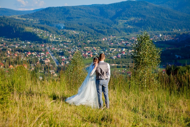 Jonggehuwden glimlachen en omhelzen elkaar tussen de wei bovenop de berg.
