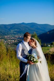 Jonggehuwden glimlachen en omhelzen elkaar tussen de weide op de top van de berg.