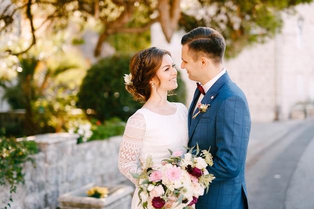 Jonggehuwden glimlachen teder naar elkaar tegen de achtergrond van groen