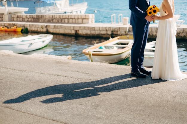 Jonggehuwden houden elkaars hand vast op zee paar hand in hand bruiloft