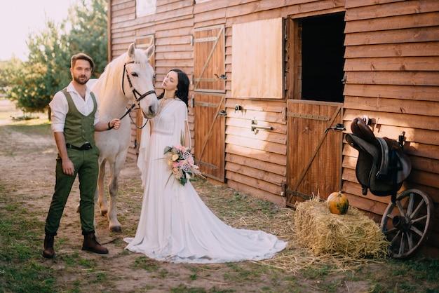 Jonggehuwden in boho-stijl die zich dichtbij paard op boerderij bevinden