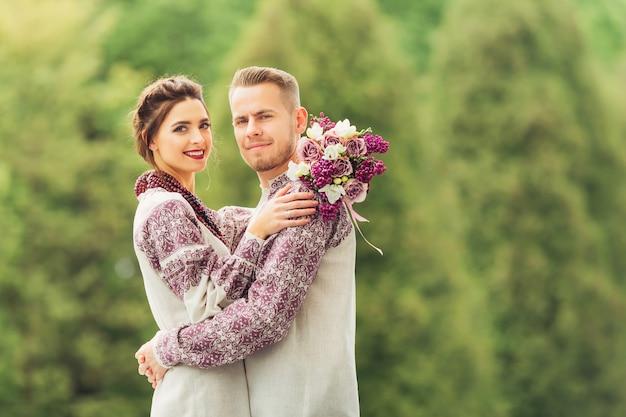Jonggehuwden in feestelijke kleding die elkaar omhelzen