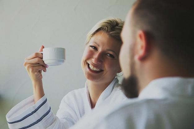 Jonggehuwden in witte hoteljassen drinken 's ochtends koffie op het balkon