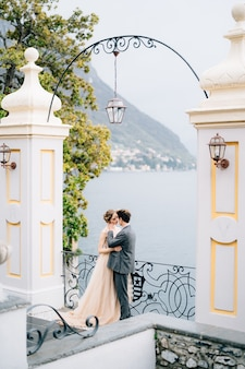 Jonggehuwden knuffelen en kussen bijna onder een oude boog tegen de achtergrond van het comomeer
