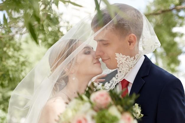 Jonggehuwden kussen in het park na de huwelijksceremonie