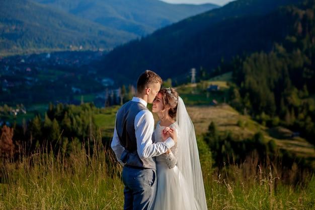 Jonggehuwden lachen en omhelzen elkaar tussen de wei bovenop de berg