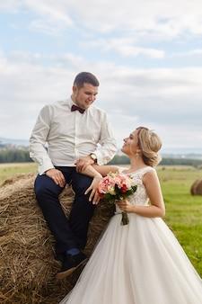 Jonggehuwden lopen en ontspannen in het veld, bruiloft