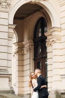 Jonggehuwden omhelzen elkaar en sluiten hun ogen, prachtig gebouw. de bruidegom kust de bruid.