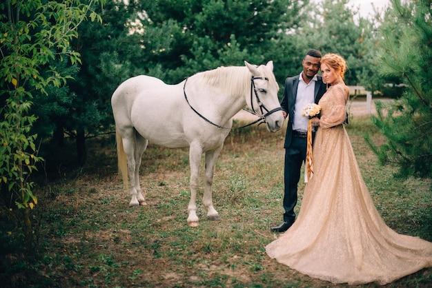 Jonggehuwden staan in de buurt van een wit paard in de natuur
